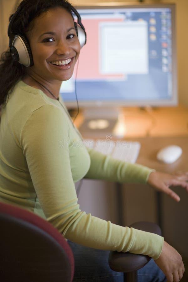 Belle femme de couleur avec des écouteurs photographie stock libre de droits