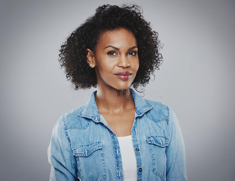 Belle femme de couleur avec la chemise de blue-jean photographie stock libre de droits