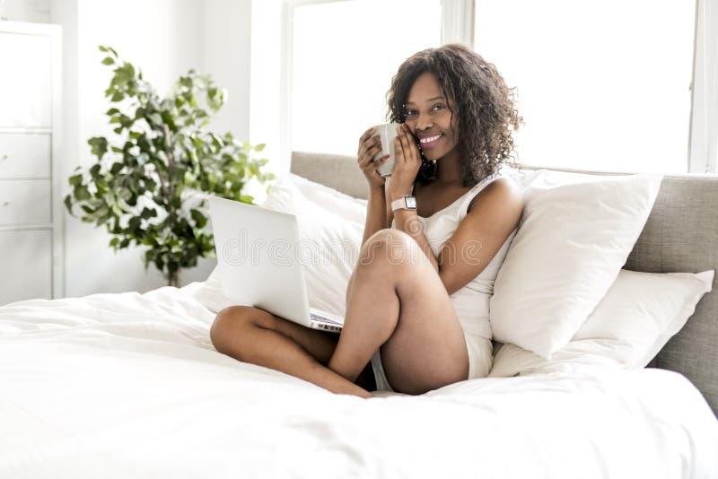 Belle femme de couleur sur un lit blanc avec l'ordinateur portable et le café photographie stock libre de droits