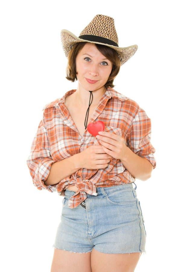 Belle femme de cowboy retenant un coeur rouge images stock
