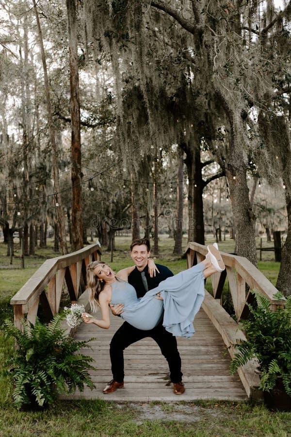Belle femme de demoiselle d'honneur dans la robe bleue et bouquet avec sa date à un événement formel de célébration de noce dehor photos stock