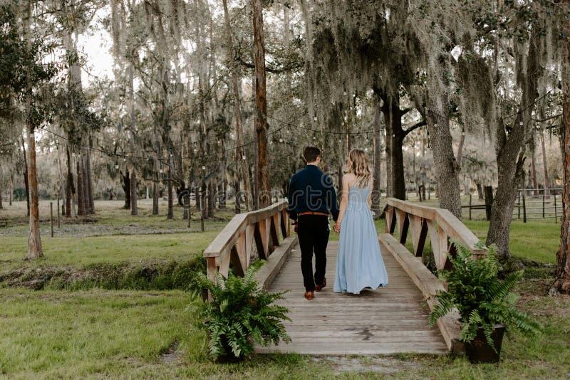 Belle femme de demoiselle d'honneur dans la robe bleue et bouquet avec sa date à un événement formel de célébration de noce dehor photos libres de droits