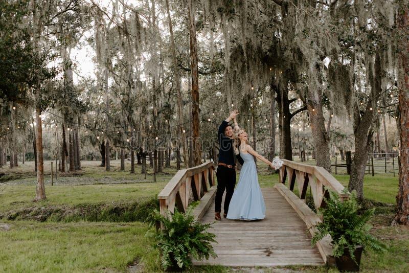 Belle femme de demoiselle d'honneur dans la robe bleue et bouquet avec sa date à un événement formel de célébration de noce dehor image stock