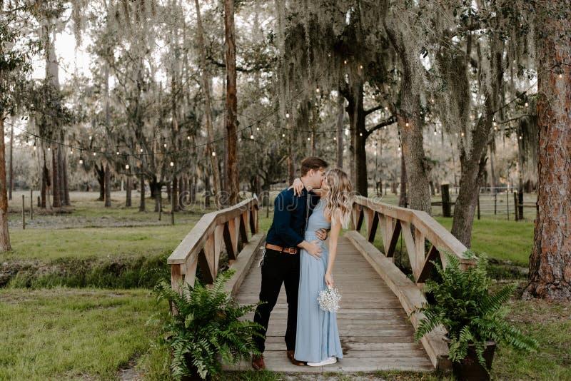 Belle femme de demoiselle d'honneur dans la robe bleue et bouquet avec sa date à un événement formel de célébration de noce dehor image libre de droits