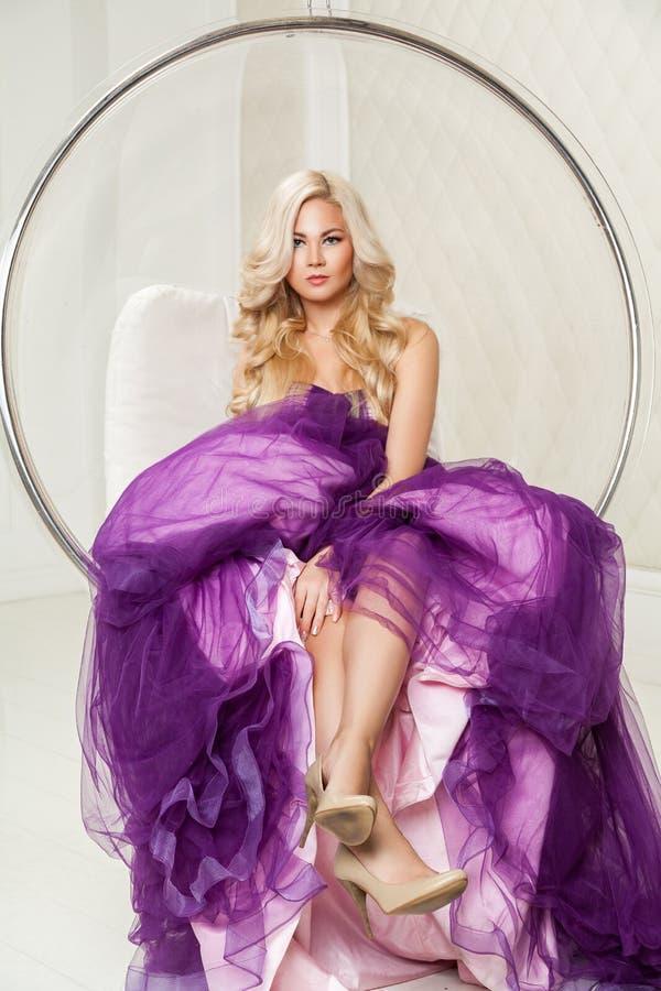 Belle femme de fantaisie blonde heureuse dans la robe pourpre gonflée à la mode avec le maquillage et la longue coiffure bouclée  image libre de droits