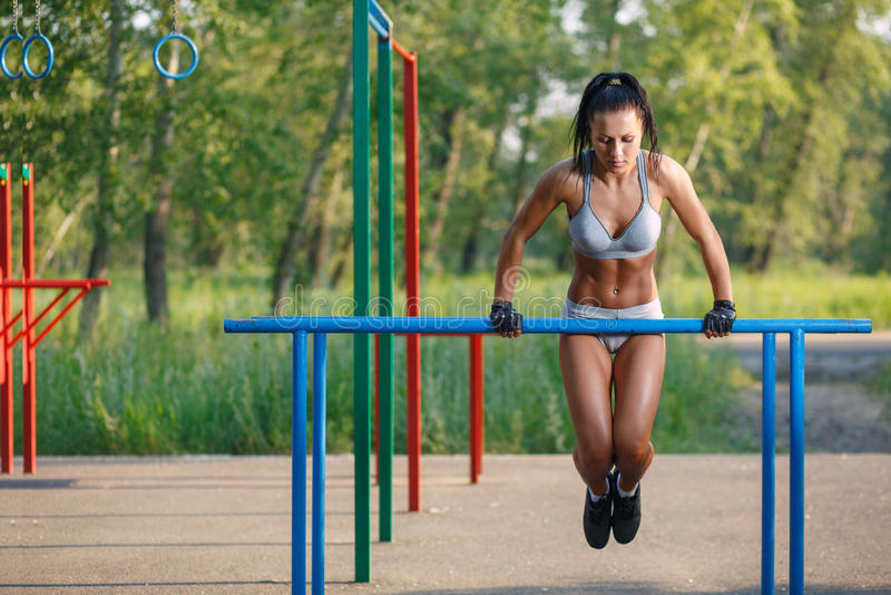 Belle femme de forme physique faisant l'exercice sur extérieur ensoleillé de barres parallèles images stock