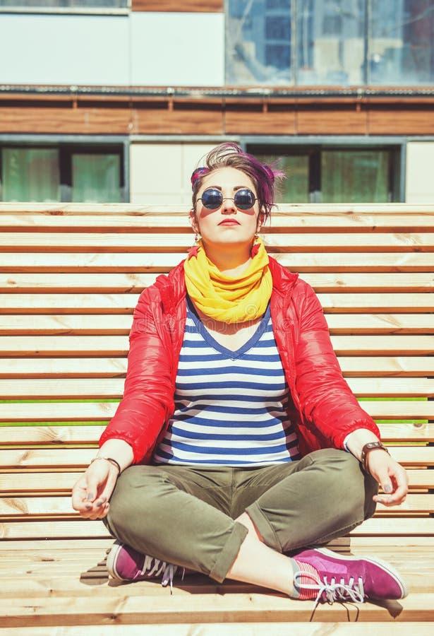 Belle femme de hippie de mode faisant le yoga sur le banc photos stock