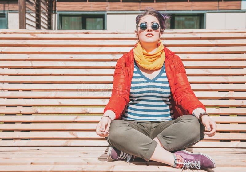 Belle femme de hippie de mode faisant le yoga sur le banc image stock