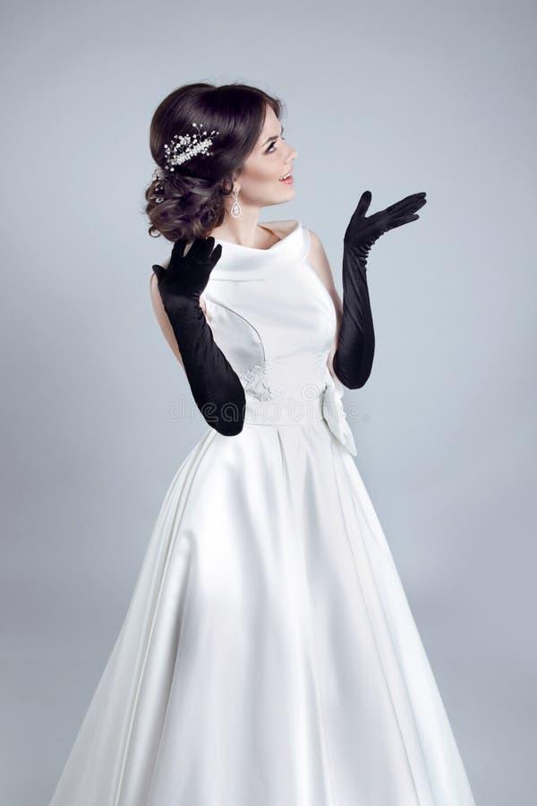 Belle femme de jeune mariée avec des gants dans la robe de mariage montrant sur op images libres de droits