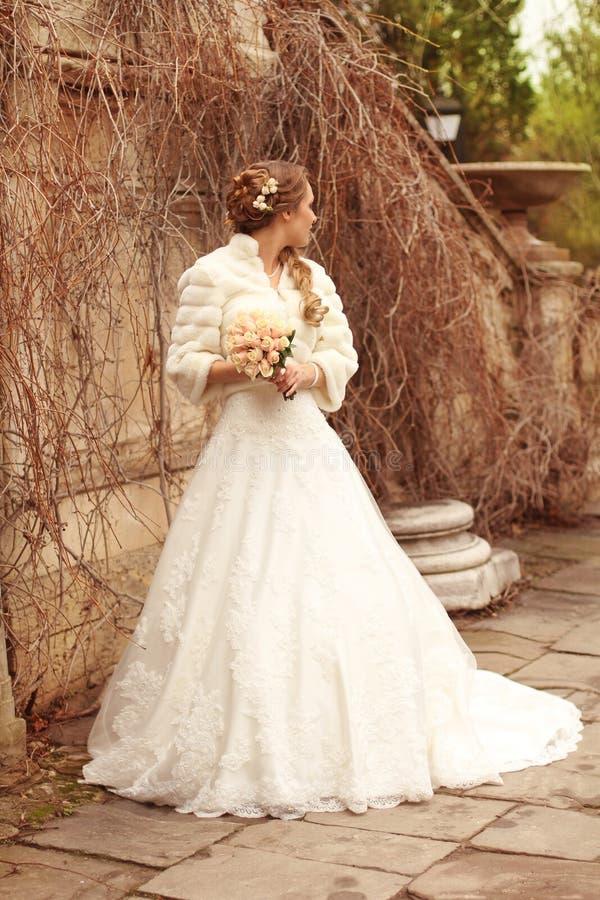 Belle femme de jeune mariée dans la robe de mariage - verticale extérieure image stock