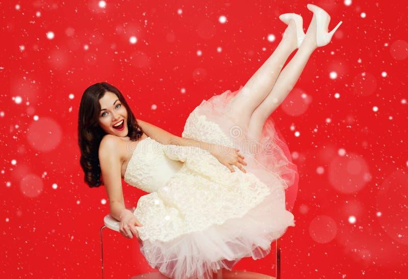 Belle femme de jeune mariée de brune de Noël dans la robe de mariage blanche ayant l'amusement sur la table au-dessus du fond rou photographie stock