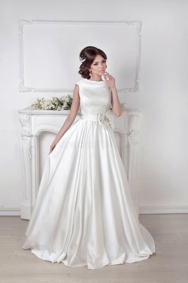 Belle femme de jeune mariée posant dans la robe magnifique au-dessus de wal blanc photos stock