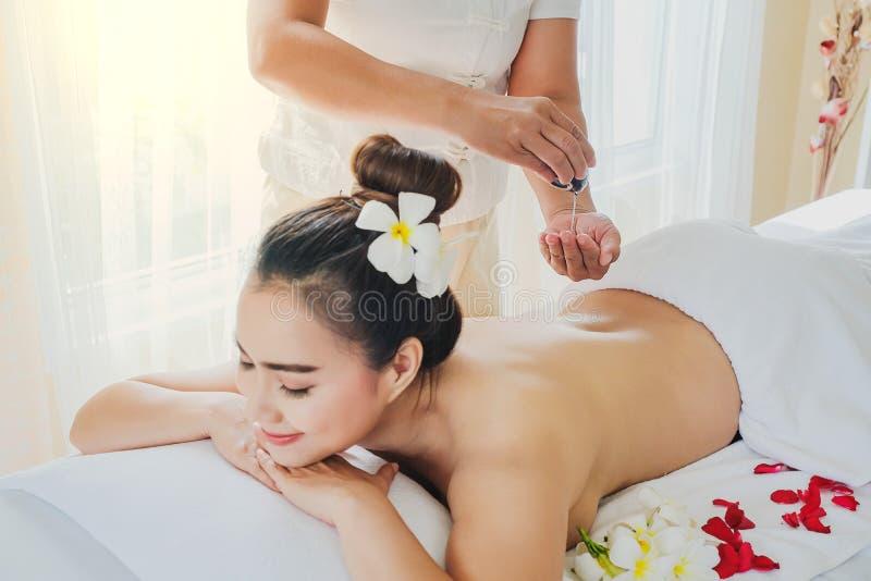Belle femme de l'Asie pendant le massage avec l'huile essentielle dans la station thermale de la chambre photo libre de droits