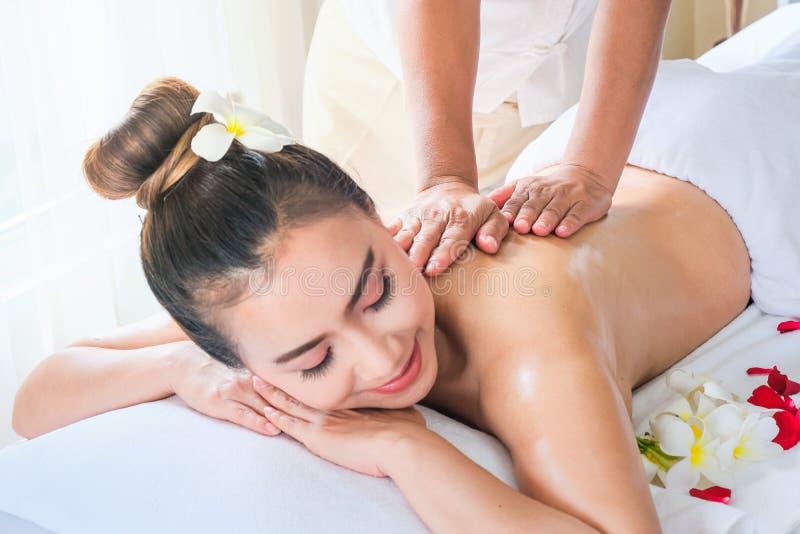 Belle femme de l'Asie pendant le massage avec l'huile essentielle dans la station thermale de la chambre photos libres de droits