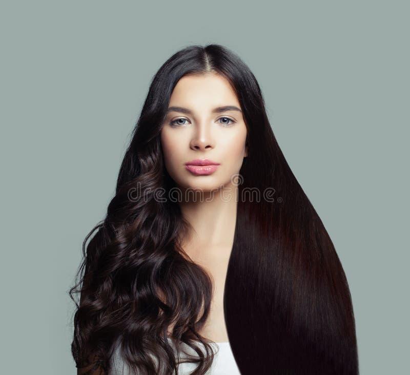 Belle femme de mannequin avec de longs cheveux droits et coiffure bouclée parfaite sur le fond bleu photographie stock