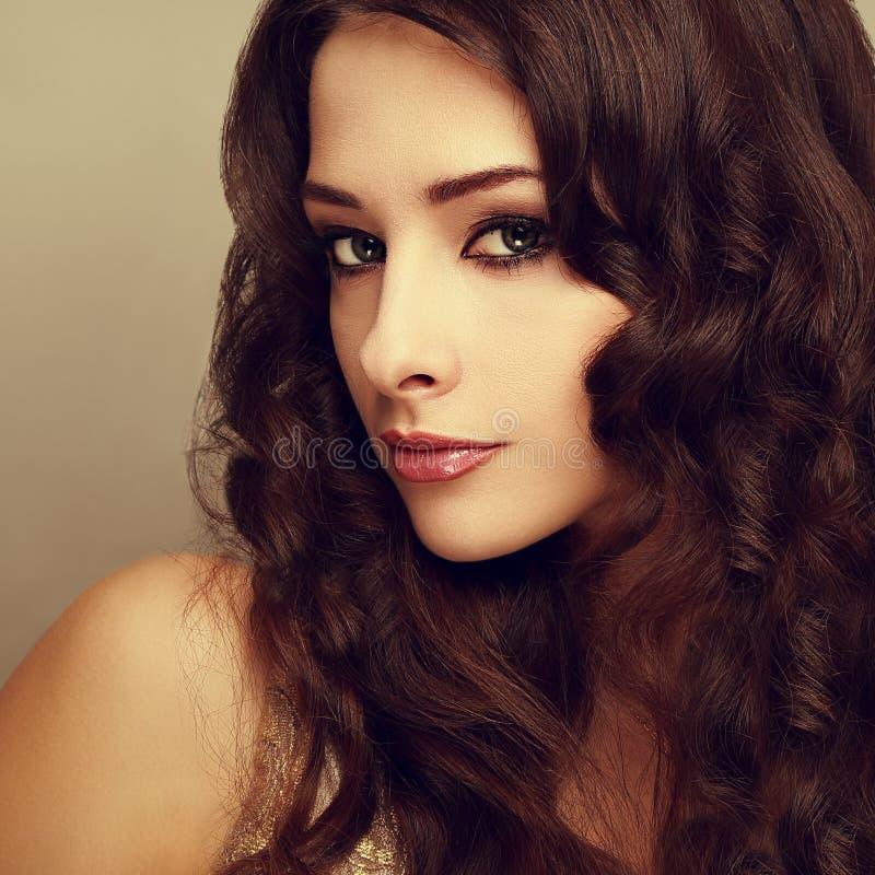 Belle femme de maquillage avec de longs cheveux bouclés brillants image stock