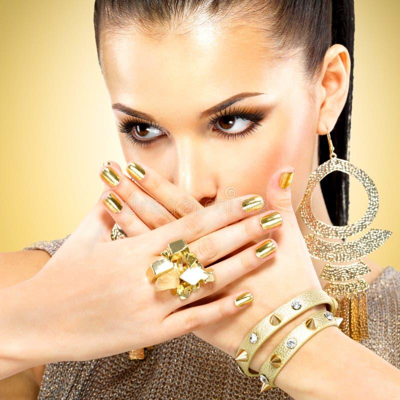 Belle femme de mode avec le maquillage noir et la manucure d'or photos libres de droits