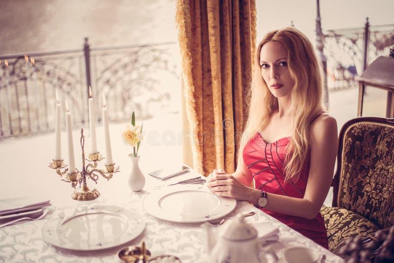 Belle femme de mode dans la robe rouge dans le restaurant image libre de droits