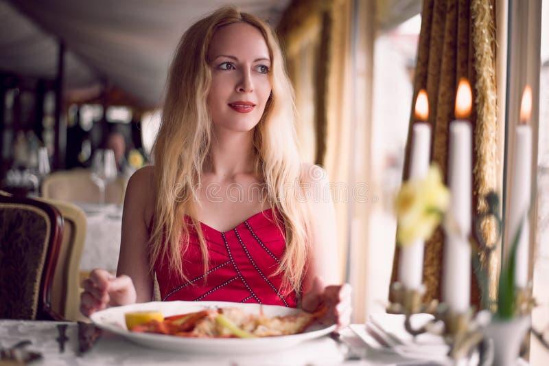 Belle femme de mode dans la robe rouge dans le restaurant photos stock