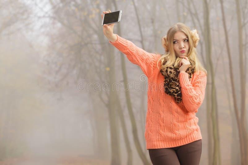 Belle femme de mode en parc prenant la photo de selfie photographie stock