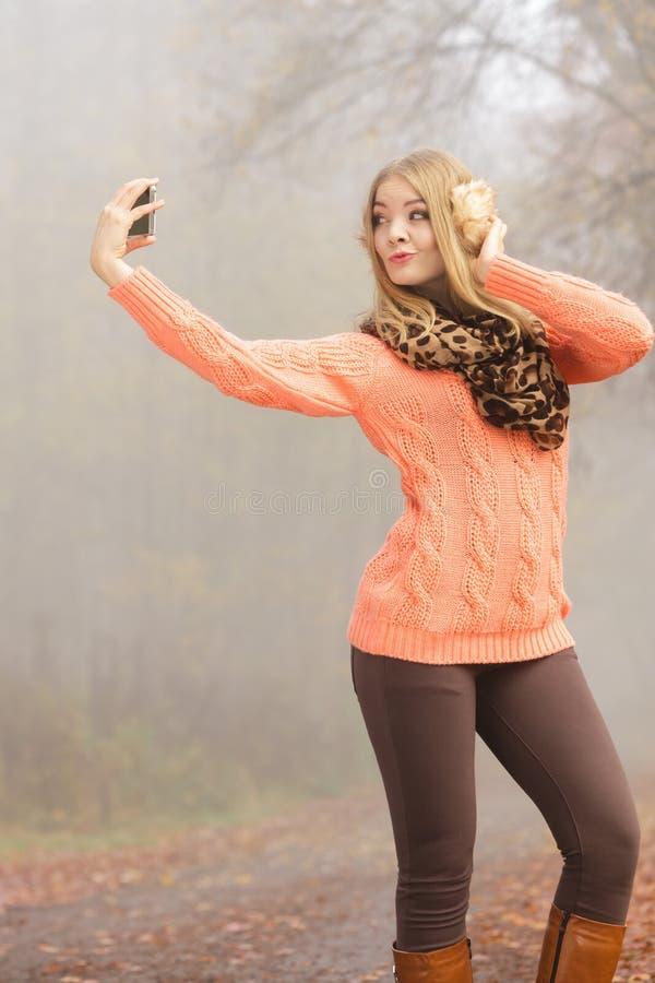 Belle femme de mode en parc prenant la photo de selfie image stock