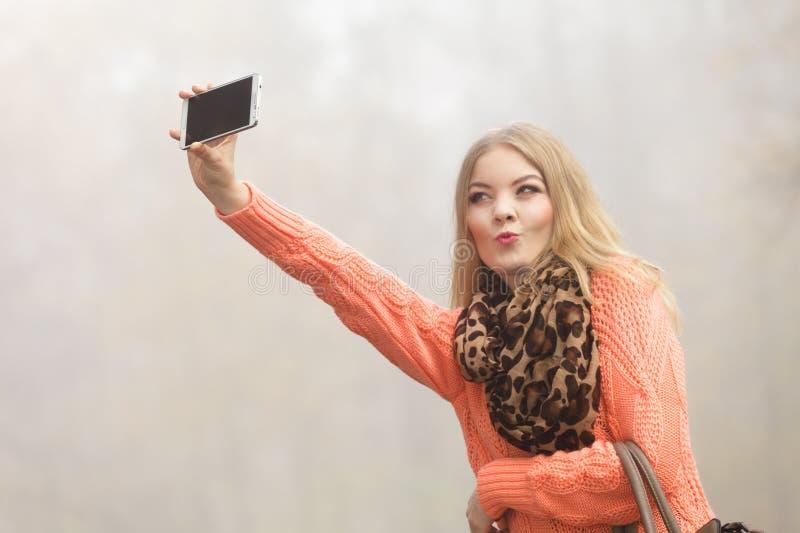 Belle femme de mode en parc prenant la photo de selfie photos stock