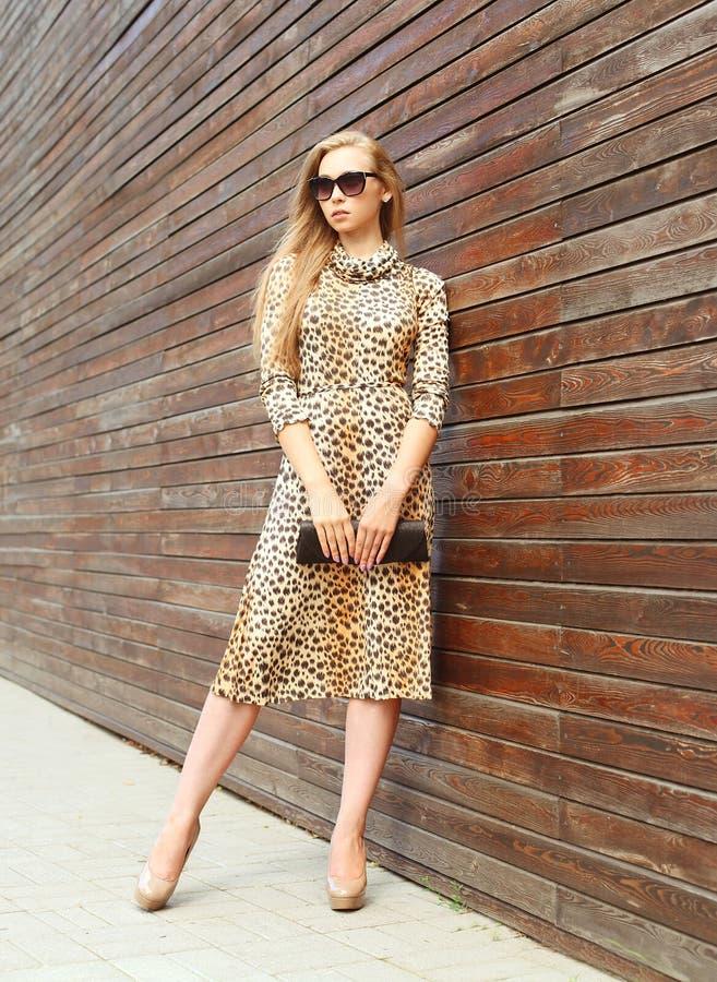 Belle femme de mode utilisant une robe et des lunettes de soleil de léopard avec l'embrayage de sac à main dans la ville images stock