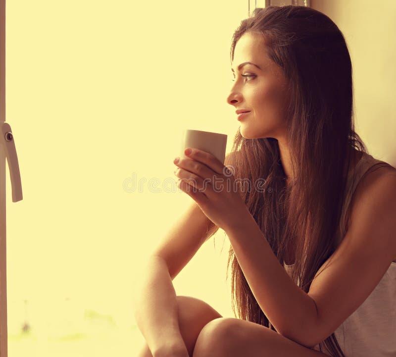 Belle femme de pensée s'asseyant près de la fenêtre et regardant le hasard photos stock