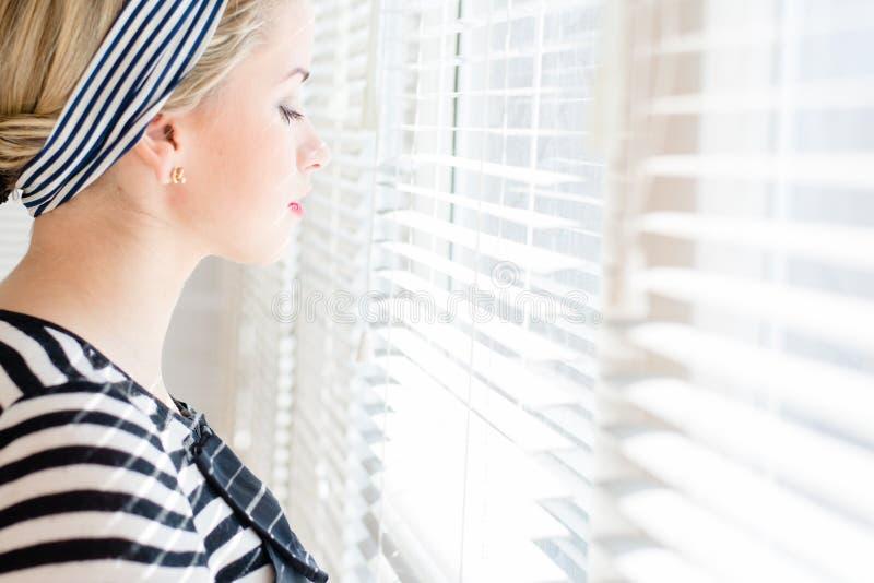 Belle femme de pin-up blonde regardant pensivement par des fenêtres de jalousie image stock