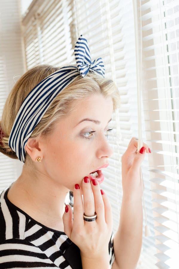 Belle femme de pin-up blonde regardant pensivement par des fenêtres de jalousie photographie stock libre de droits
