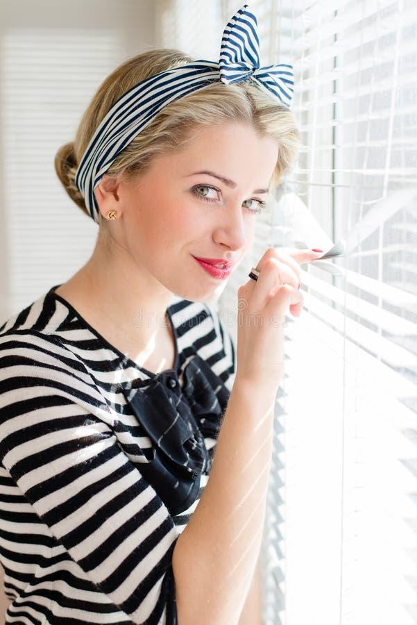 Belle femme de pin-up blonde regardant pensivement par des fenêtres de jalousie image libre de droits