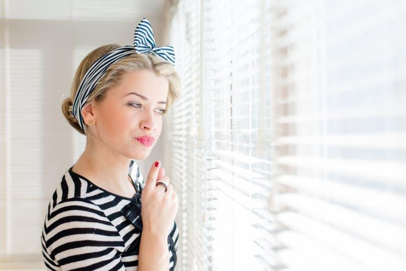 Belle femme de pin-up blonde regardant pensivement par des fenêtres de jalousie photo libre de droits