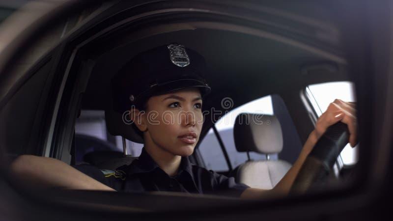 Belle femme de police conduisant la voiture, surveillant l'ordre public du trafic dans la ville photos stock