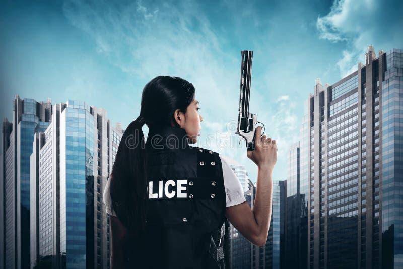 Belle femme de police tenant l'arme à feu photographie stock libre de droits