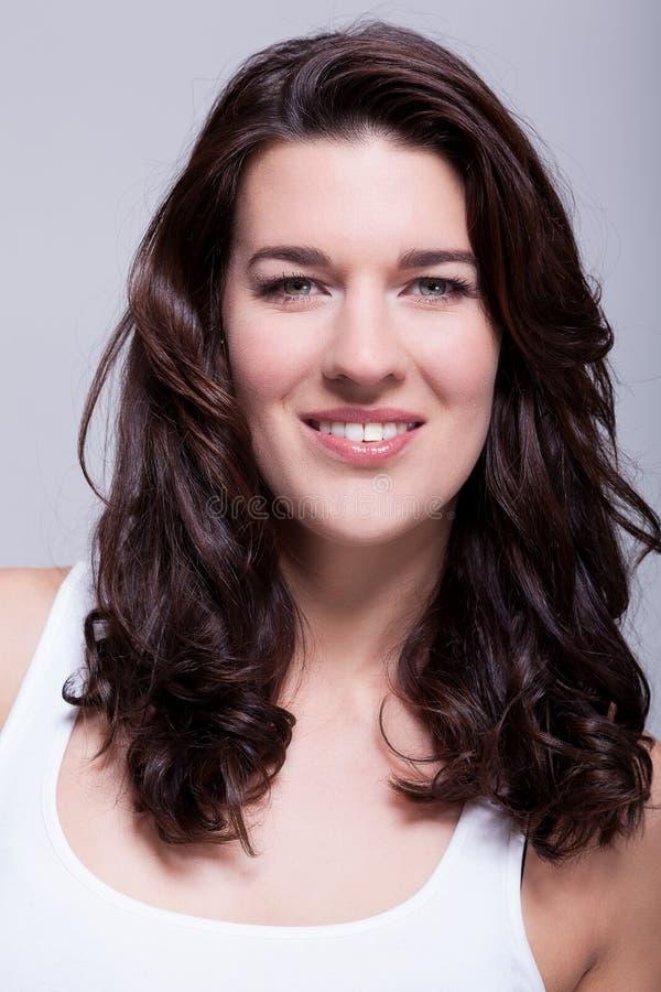 Belle femme de portrait avec les cheveux foncés souriant dans l'appareil-photo images stock