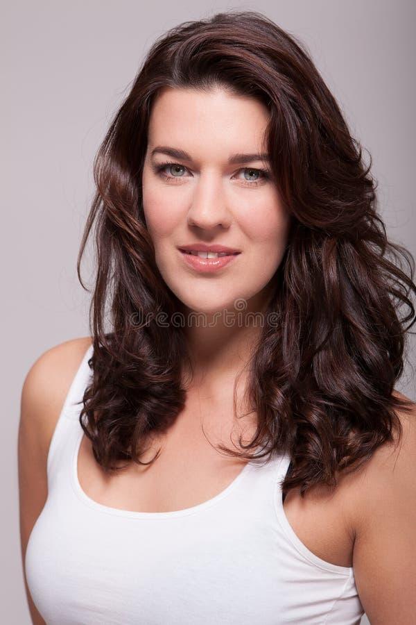 Belle femme de portrait avec les cheveux foncés souriant dans l'appareil-photo photographie stock