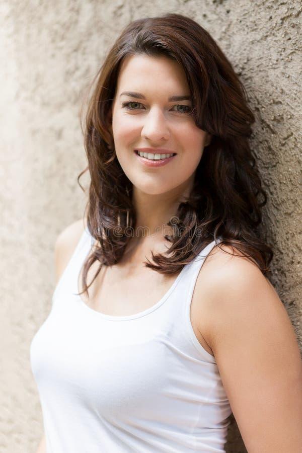 Belle femme de portrait avec les cheveux foncés souriant dans l'appareil-photo photos libres de droits