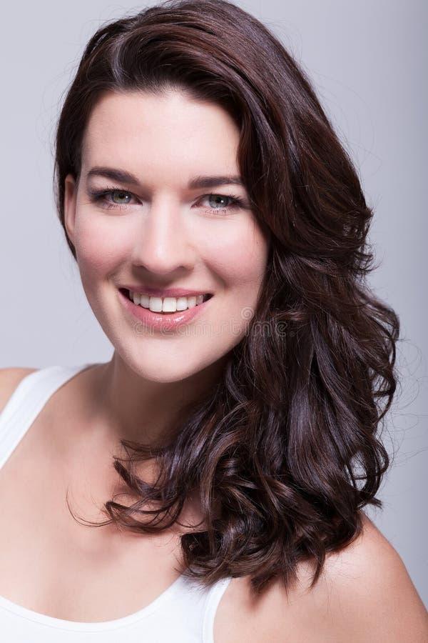 Belle femme de portrait avec les cheveux foncés souriant dans l'appareil-photo image stock