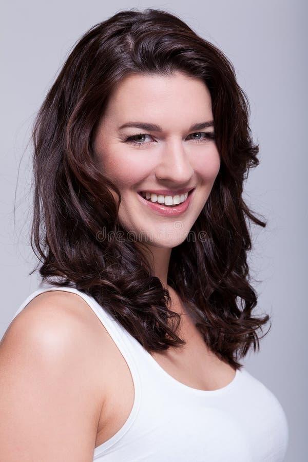 Belle femme de portrait avec les cheveux foncés souriant dans l'appareil-photo photos stock