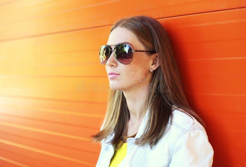 Belle femme de portrait dans des lunettes de soleil au-dessus de fond orange photographie stock