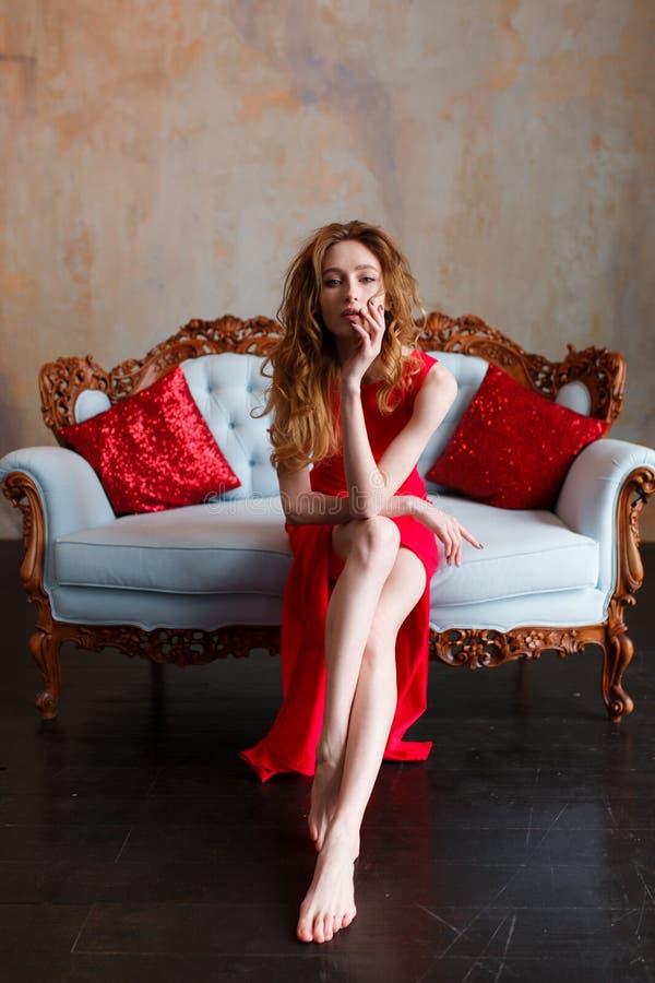 Belle femme de redhair élégant sexy sur sofa classique de tissu le rétro photos libres de droits