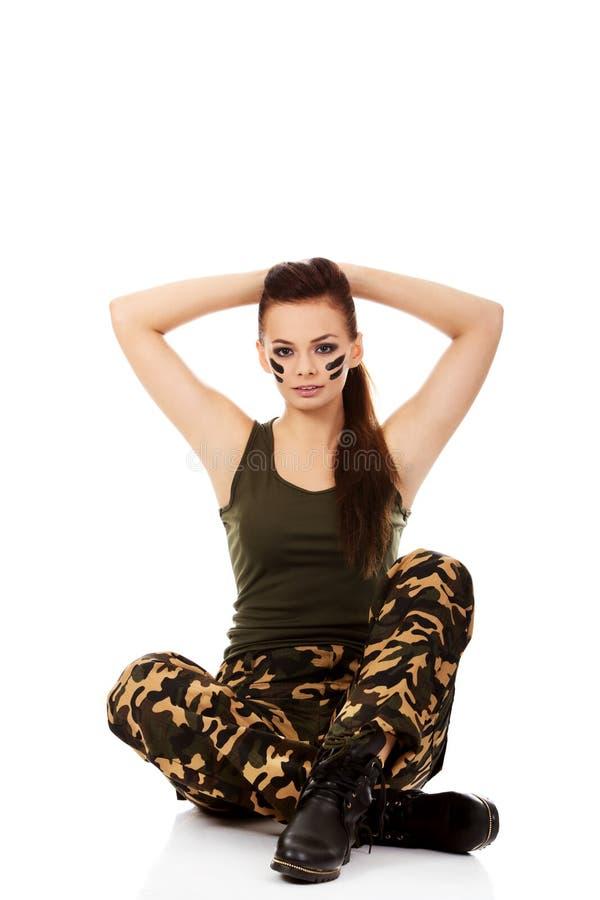 Belle femme de soldat de Ypung s'asseyant sur le plancher image stock
