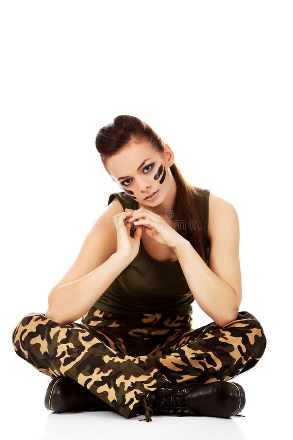 Belle femme de soldat de Ypung s'asseyant sur le plancher images stock