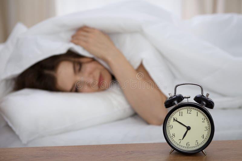Belle femme de sommeil se situant dans le lit et essayant de se réveiller avec le réveil Fille ayant des ennuis avec se lever tôt images stock