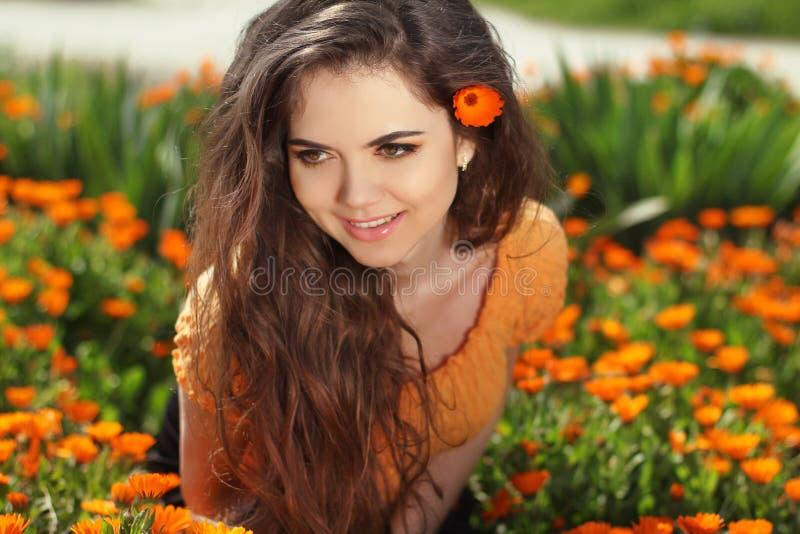 Belle femme de sourire avec de longs cheveux sains au-dessus des fleurs,  photo stock