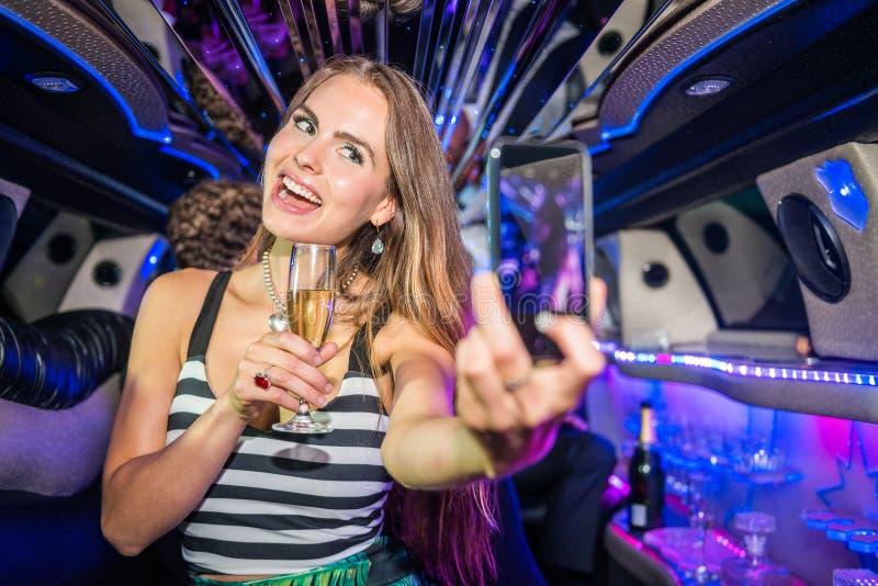 Belle femme de sourire avec la cannelure de champagne prenant le selfie le MOIS image libre de droits