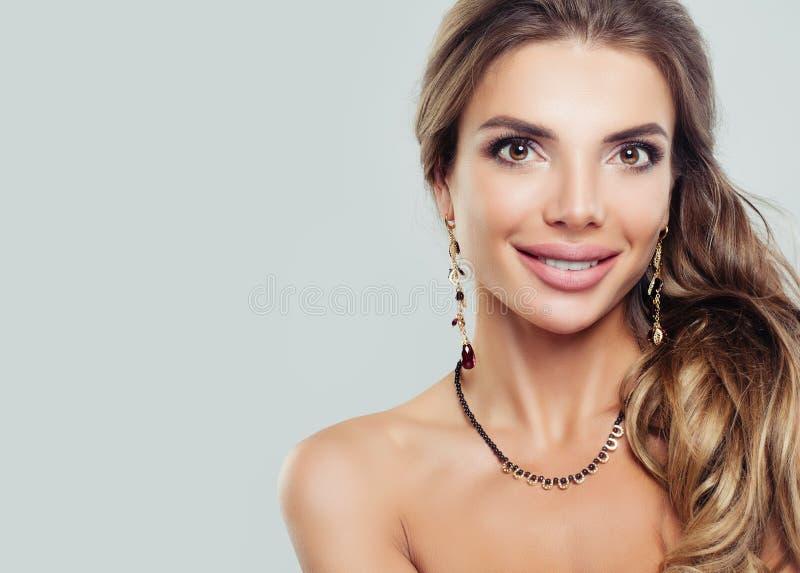 Belle femme de sourire avec le collier et les boucles d'oreille de bijoux images stock