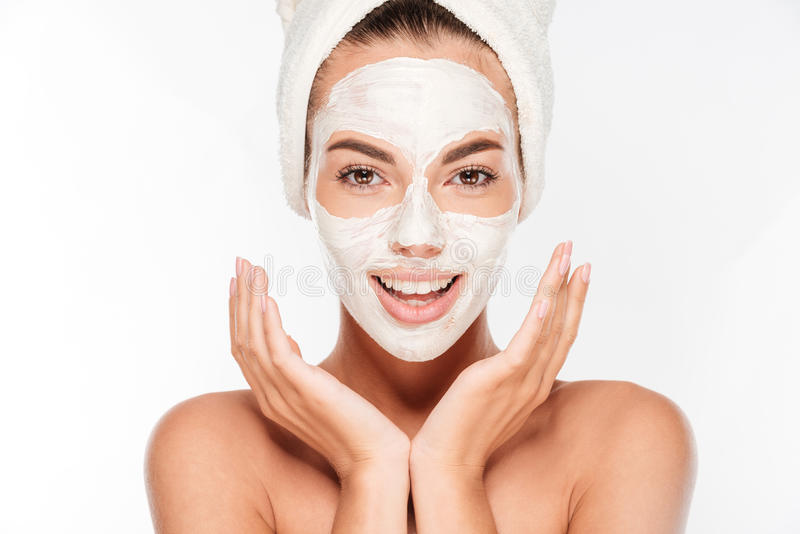 Belle femme de sourire avec le masque facial d'argile blanc sur le visage images stock