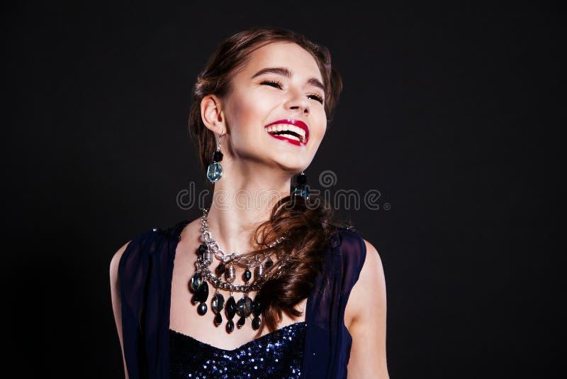 Belle femme de sourire avec les bijoux de port de maquillage parfait de soirée image stock
