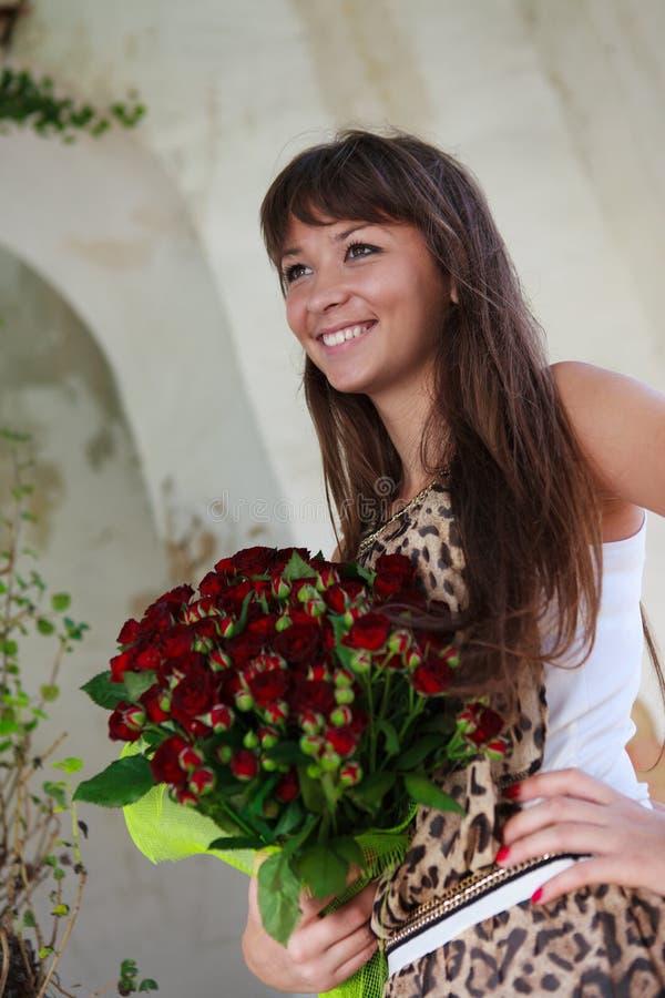 Belle femme de sourire avec un bouquet des roses rouges photographie stock libre de droits